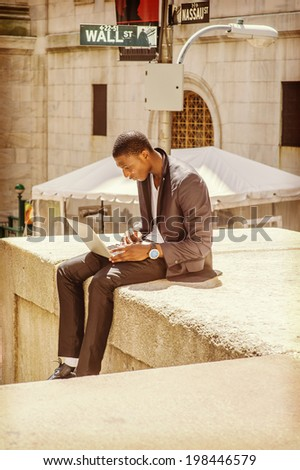 Young man working on street. A young black college guy is sitting outside, looking down, working on a laptop computer. Wall Street sign in the background. - stock photo