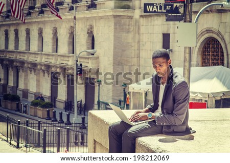 Young man working on street. A young black college student is sitting outside, working on a laptop computer, looking down, thinking.  Wall Street sign in the background. - stock photo