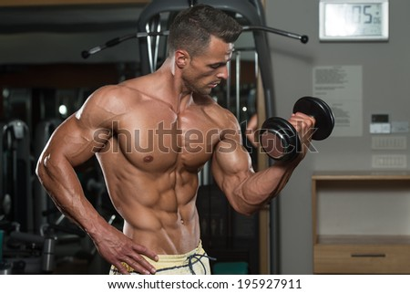 Young Man Working Out Biceps - Dumbbell Concentration Curls - stock photo