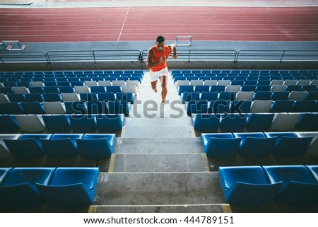 Young man working out on stadium tribune steps - stock photo