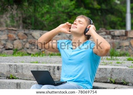 Young man working with a laptop and listening music on headphone outdoors - stock photo
