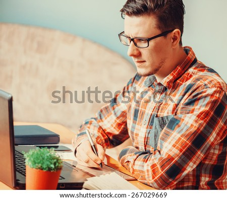 Young man working with graphics tablet over laptop in the office - stock photo