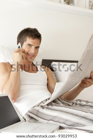 Young man working with laptop and cell phone in bed, and reading a newspaper. - stock photo