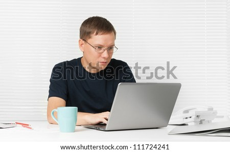 young man working with laptop at his desk - stock photo