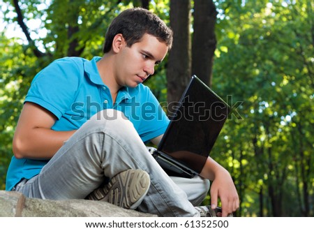 young man working with laptop in the park - stock photo