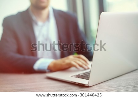 Young man working with laptop, man's hands on notebook computer, business person at workplace - stock photo