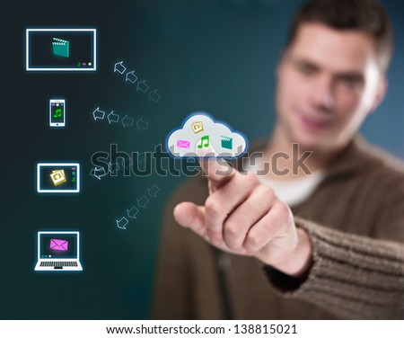 Young man working with multimedia cloud - stock photo