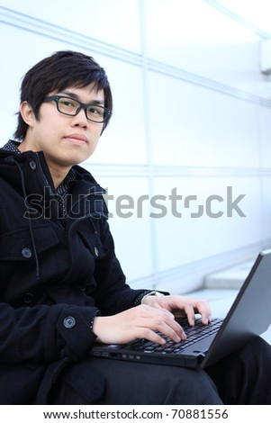 young man works for a laptop at outdoor - stock photo