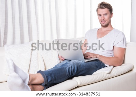 young man works with laptop on couch