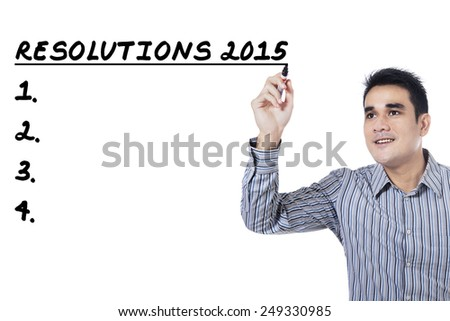 Young man writes his resolutions in 2015, isolated over white background