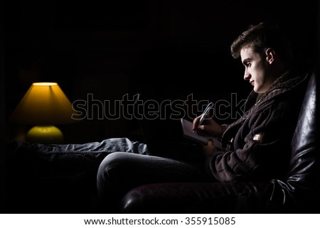 Young man writing and practicing for exam at home.People, education, session, exams and school concept - tired student man or young man with book. The night before the exam - stock photo
