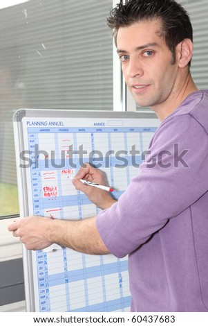 Young man writing down on a schedule board