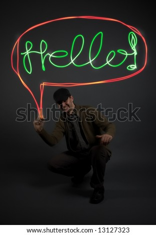"Young man writing the word ""Hello"" with light in the air, model is underexposed/ low-key to allow for the letters to stand out - stock photo"