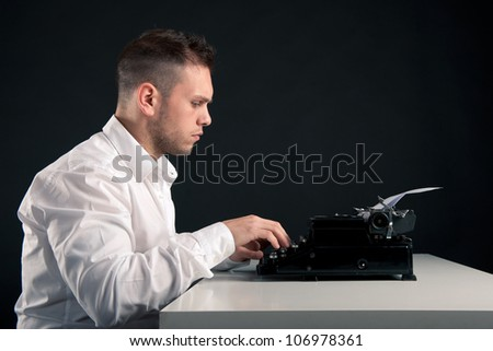 Young man writing with an old typewriter. Retro image with copy space on black background. - stock photo