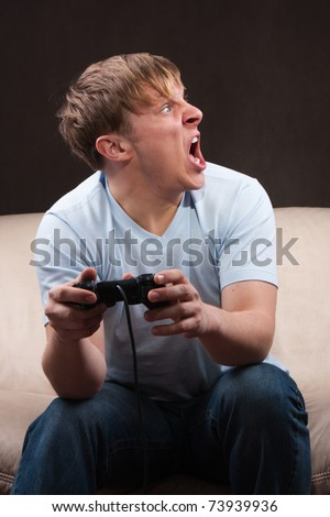 young man yelling at someone while playing video games on gray background - stock photo