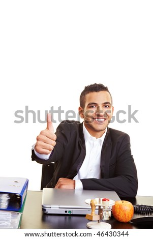 Young manager at his desk holding his thumb up - stock photo