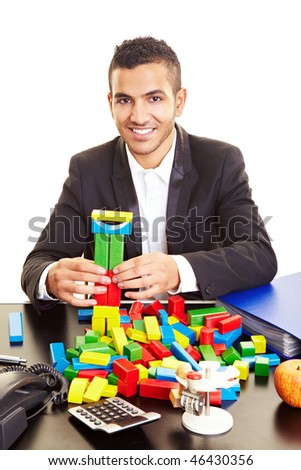 Young manager at his desk playing with colorful building bricks