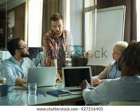 Young manager expressing his opinion at meeting - stock photo