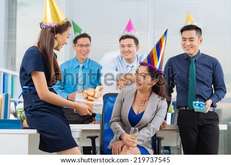 Young manager giving birthday present to her colleague at the office party - stock photo