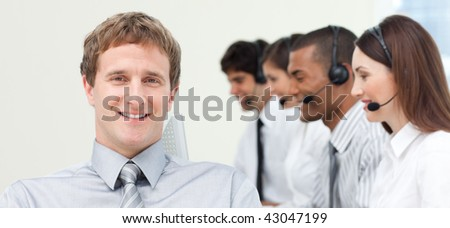 Young manager in front of his team in a call center - stock photo