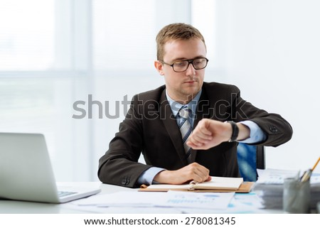 Young manager looking at watch on his hand - stock photo