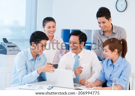 Young manager presenting his idea on the laptop to his colleagues - stock photo