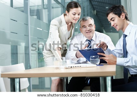 Young manager showing plan to his colleagues - stock photo