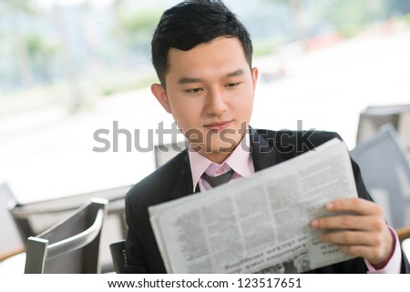 Young manager spending time reading business news