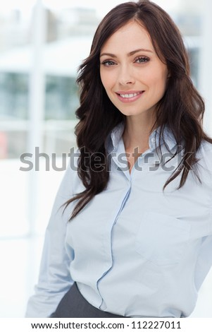Young manager standing upright in front of the window while smiling - stock photo
