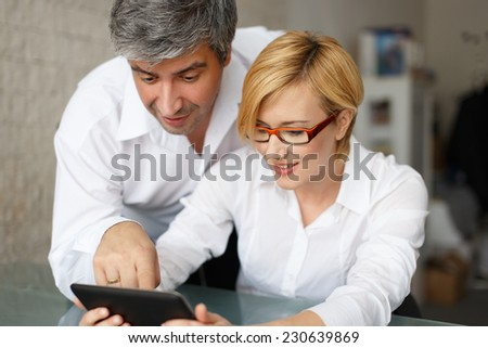 Young managers analyzing results on tablet in office - stock photo