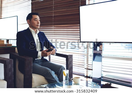 Young managing director using smart phone while sitting in modern office near publicly blank tv screen with copy space,successful businessman waiting for a call on his cell telephone during breakfast  - stock photo