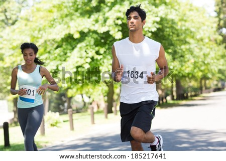 Young marathon athletes running on country road - stock photo
