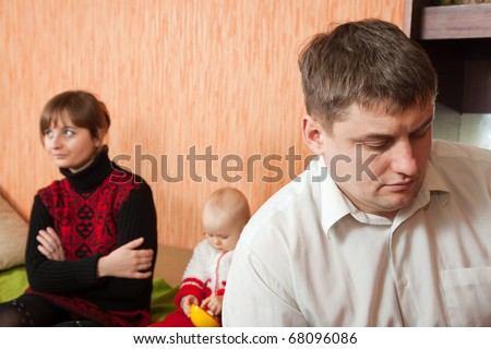 young marriage quarreling at home. Their baby sitting between them - stock photo