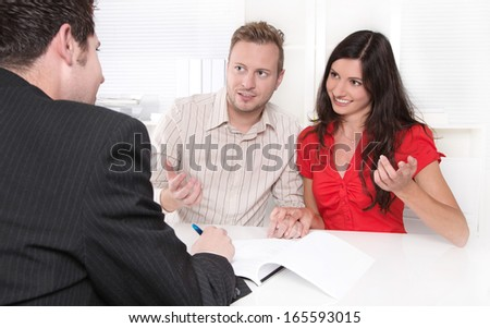 Young married couple at desk in a business meeting - stock photo