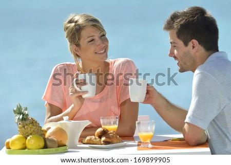 Young married couple enjoying breakfast - stock photo