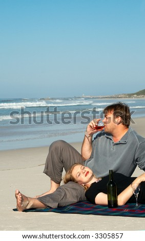 Young married couple enjoying their vacation on the beach in South Africa. The man is drinking wine, while the lady is lying down on his lap. Shot on a sunny day with blue sky in the background.