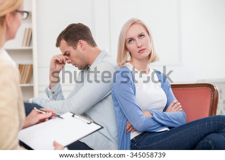 Young married couple has problems in their relationship. They are sitting in office of psychologist with insult. The woman is listening to them and making notes