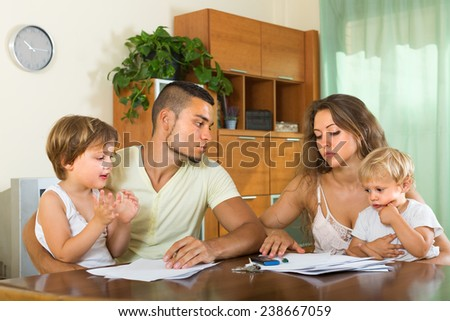 Young married couple having quarrel in front of children at home - stock photo
