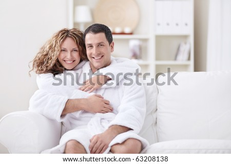Young married couple in dressing gowns at home - stock photo