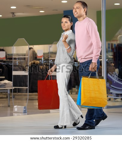 Young married couple in shop against show-windows