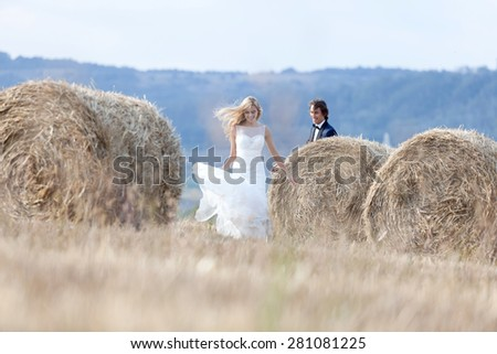 Young married couple playing like kids, running between hay bales. - stock photo
