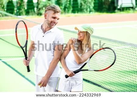 Young married couple playing tennis in white sportwear on the tennis court outside in the summer