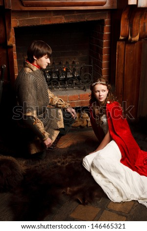 Young married couple sitting near the fireplace.Looking like Romeo and Juliet - stock photo