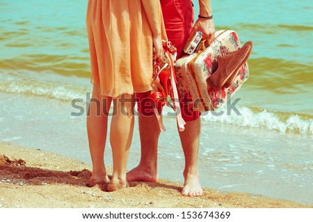 Young married couple standing together on beach holding their photo camera and shoes. Sunny summer day. Copy-space. Outdoor shot - stock photo