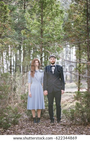 Young married couple stands in the summer sunset forest, holding hands, looking weird. Beautiful redhead bride in a blue dress and a bearded groom in a suit with a bow tie