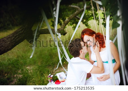 Young married couple walking in the park. Young beautiful pregnant woman hugging her husband. - stock photo