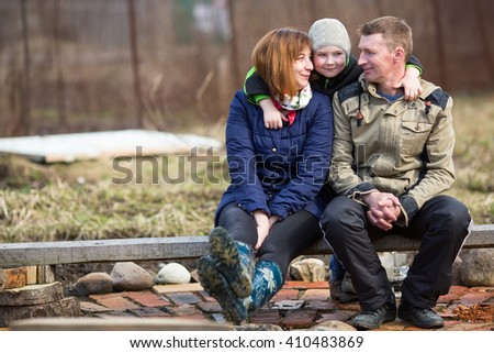 Young married couple with a young son sitting outdoors.