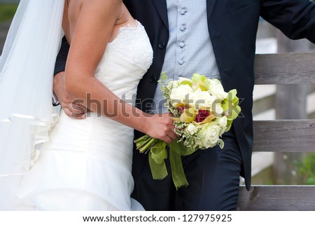 Young married couple with bride holding a flower bouquet - stock photo