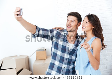 Young married happy couple making selfie holding keys in new flat - stock photo