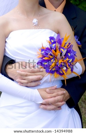 young marrieds are together  holding wedding bouquet